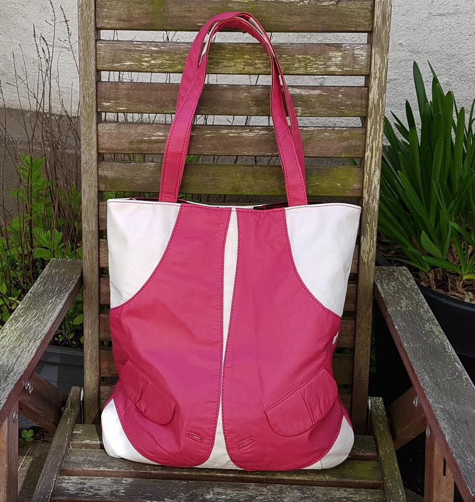Hvid og Pink shopper ud af en meget lille jakke og hvide ærmer fra en anden jakke.